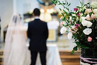 Vase of flowers in the church and in the background the bride and groom at the altar