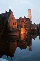 Buildings along the water illuminated at dusk; Bruges, Belgium