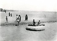 Natives on the Tigris near Baghdad, Iraq, with a gufa or guffa, a round wickerwork boat used since ancient times.