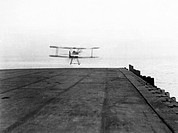 A Sopwith Pup biplane taking off from the deck of the aircraft carrier HMS Furious (a modified Courageous-class cruiser) during the First World War. L...
