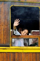 Loughing girl looking out of a historic steam train at Paranapiacaba station; near Sao Paulo, Brazil. In 1856 the British-owned Sao Paulo Railway Comp...