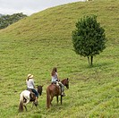 A Girl And Her Mother Riding Horseback Through The Hills; Finca El Cisne, Honduras