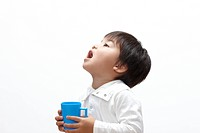 Young boy gargling with mouthwash
