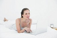 Thoughtful casual woman using laptop in bed