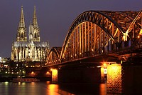 Cologne Cathedral and Hohenzollern Bridge at night along the Rhine river , Germany.