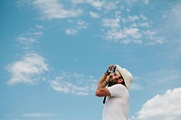 Man taking a photograph of clouds and sky.