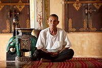 Old man meditating in a pagoda in Siem Reap Cambodia.