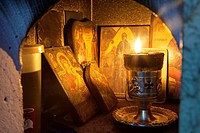 A lit candle and Icons inside a Religious Shrine ( Eklisaki ) Crete, Greece.