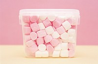 White and pink marshmallows inside of a plastic container