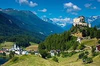 Tarasp Castle and Fontana village surrounded by larch forest in the Lower Engadine Valley, Switzerland, Europe