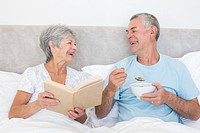 Happy couple with book and bowl in bed