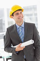 Happy architect smiling and holding blueprints