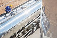 Worker on platform above stainless steel milk tanker