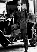 Umberto Orsini in the film The Assassination of Matteotti. The Italian actor Umberto Orsini with a walking stick in his hand leaning on a car in the f...