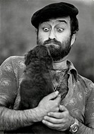 Lucio Dalla grimacing at a dog. Italian singer, songwriter and musician Lucio Dalla grimacing at the dog that he's holding. Sorrento, 1970s