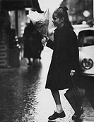 The baby girl poetess, Minou Drouet, walking. The French baby girl poetess, Minou Drouet, walking with an umbrella in her left hand and a bunch of flo...