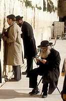 An old jewish pilgrim, with a long gray beard sits by the Wailing Wall, committed in reading the Torah in total contemplation while two others, younge...