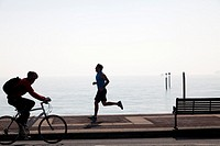 Cyclist and jogger on Southsea Promenade.