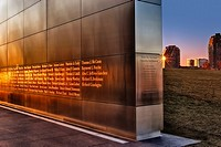 Empty Sky September 11th Memorial at sunset, located in Liberty State Park, New Jersey.The golden sun brightly illuminates the names of the victims fr...