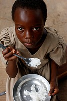 African girl eating rice, Lome, Togo.