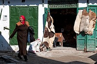 Woman in traditional clothing passing by a animal hides shop in the medina streets, Tetuan, Morocco.