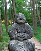 D-Worpswede, Hamme, Teufelsmoor, Niedersachsen, Kuenstlerdorf, Skulptur -Humor- von Bildhauer Bernhard HoetBuddhastatue, Buddha sitzt und haelt sich d...