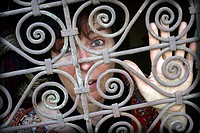 Young woman looking through a fence of a window in the Medina of Fez, Morocco, Africa.
