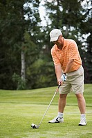 Golfer concentrating on hitting the ball at tee off; Edmonton, Alberta, Canada