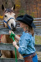 Cowgirl interacting with Paint horse at ranch in the US.