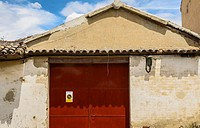 View of an orange gate of a house, Chinchon village, Madrid province, Spain.