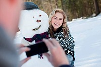 Man photographing woman beside snowman