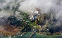 aerial view through the clouds to island Herreninsel with Old Palace and footbridge, Germany, Bavaria, Lake Chiemsee
