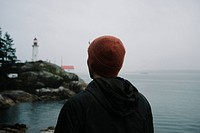 Rear view of man looking at lighthouse by sea