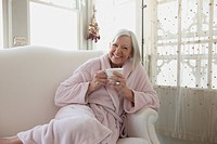 Senior Caucasian woman drinking coffee in bathrobe