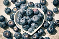Heart-shaped bowl of blueberries on wood