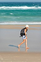 Australia, New South Wales, Pottsville, girl with backpack walking on beach