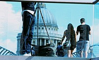 View through engraved glass of man with tripod and tourists crossing Millennium Bridge towards St Paul´s Cathedral, London, England, Europe.