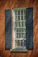 Traditional window with white frame, black shutters.