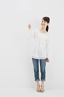 Japanese young woman in jeans and white shirt standing against white background