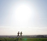 Two joggers running on hill with low sun.
