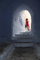 Woman posing at a passageway in Pyrgos town, Santorini, Cyclades Islands, Greek Islands, Greece, Europe.