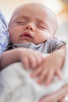 Close up of baby boy (2-5 months) sleeping in mother's arms