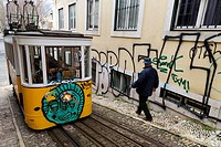 A man passing an old traditional funicular tram covered in graffiti in the historic city of Lisbon.