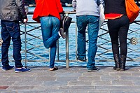 Four people leaning on a railing in Geneva, Switzerland.