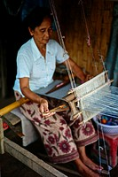 Woman woving Lao Silk using a traditional wooden machine in Ban Xang Hai, known as Whiskey Town.