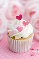 Cupcake decorated with frosting and pink sugar hearts