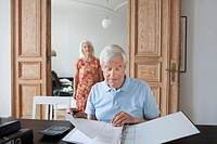 Senior man reviewing financial documents with woman in background at home