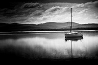 Black and white holiday landscape of a yacht sailing boat with sails down parked in Port Sorell bay at nightfall. Taken Tasmania, Australia.
