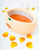 Orange parrafin wax in bowl. Manicure in beauty spa salon.