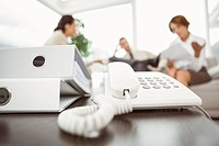 Executives with land line phone and folders in foreground